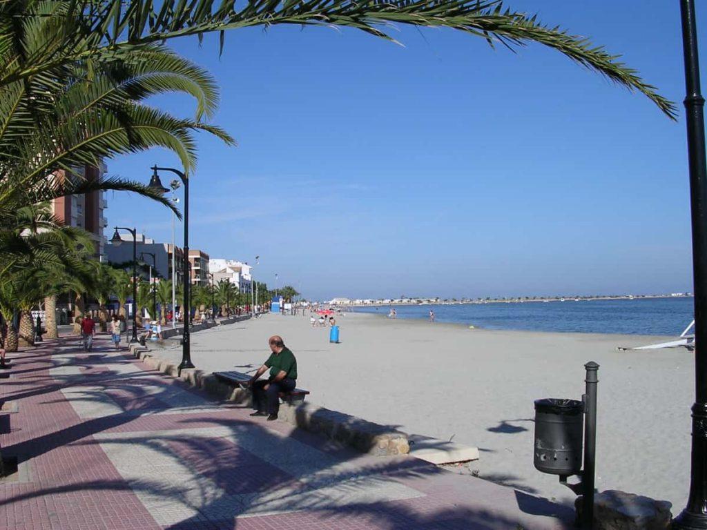 homme assis au bord d'une plage à costa calida