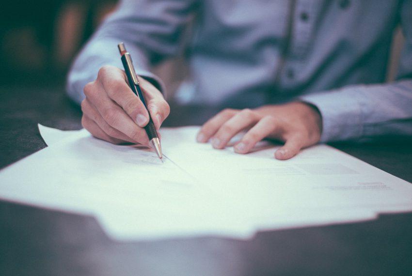 Homme signant un contrat de vente immobilier