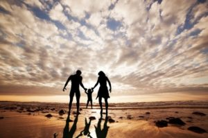 Famille profitant de leur résidence secondaire en Espagne marchant sur une plage avec un enfant