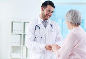 Docteur espagnol tenant la main d'une femme retraitée, lui souriant et la rassurant