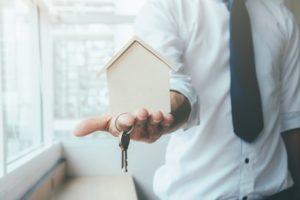 Représentation d'un homme tenant une maison dans la main, avec la clé d'une retraite en Espagne.