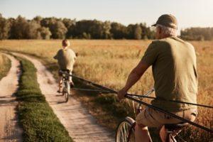 Retraité se promenant à vélo avec son petit fils sur un chemin dans la campagne espagnole